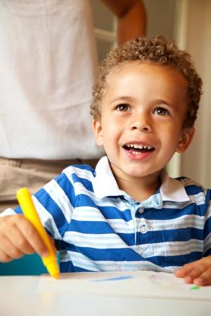 infante: Edad preescolar que parece feliz y divertirse mientras se hace una actividad de colorear en la clase Foto de archivo