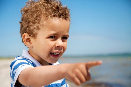 child finger: Adorable little kid pointing at something interesting outdoors Stock Photo