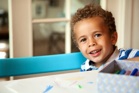 Smiling African American boy sitting on a chair and getting ready for his lesson photo