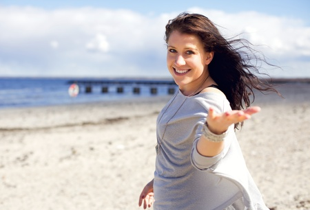 facing to camera: Woman walking on a beach in sunlight inviting you to come walk with her Stock Photo