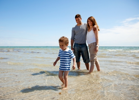 family beach: Young family enjoying the weekend on a sunny beach