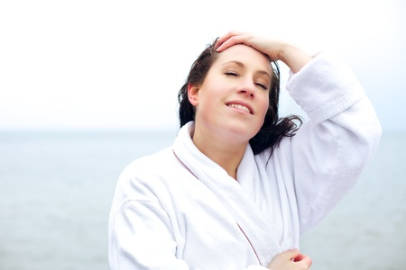 bath robes: Young woman in a bathrobe  at the beach looking relaxed after a spa treatment