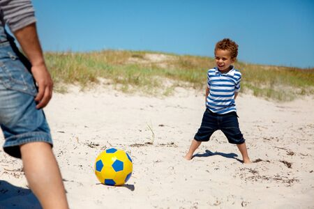 Little kid having fun and playing football with his dad on a summer vacation photo