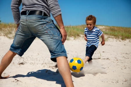 Father together with his young son playing football on the beach photo
