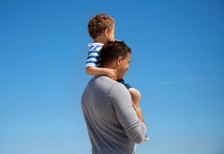 Young boy carried by his father against the blue background photo