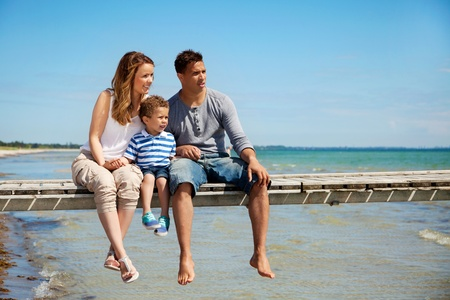 multiracial family: Small family of three enjoying their summer vacation by the beach
