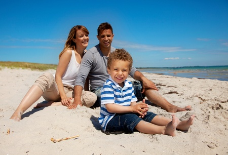 Mixed race family enjoys the weekend on a beach photo