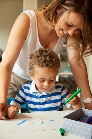 Young preschool teacher looking at what the little kid is drawing Stock Photo - 15382131