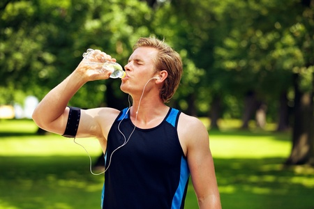 Thirsty athlete drinking water after workout photo