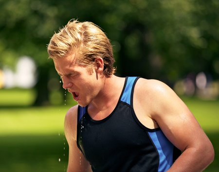 stamina: Young athlete refreshes himself with water after practice on a hot summer at the park