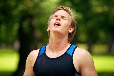 sudoroso: Atleta sudoroso joven mirando hacia arriba despu�s de un entrenamiento agotador