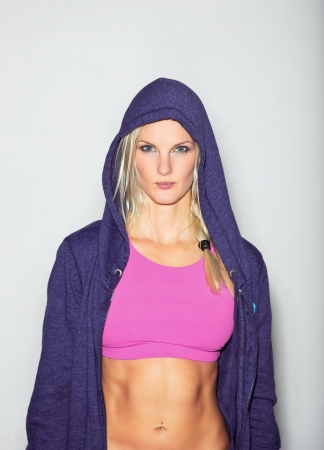 Confident woman in sportswear posing for camera against white background  photo