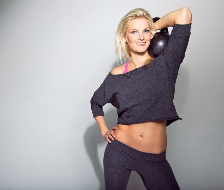 kettle bell: Cute crossfit girl with kettlebell smiling at the camera