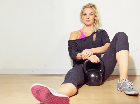 crossfit: Portrait of healthy crossfit girl relaxing in the gym with kettlebell