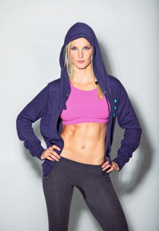 hoodie: Confident woman in sportswear posing for camera against white background