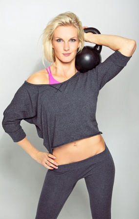 Vertical portrait of young healthy crossfit girl holding a kettlebell   Stock Photo - 15865248