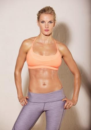 sudoroso: Mujer atractiva en el gimnasio con cuerpo en forma posando sobre fondo blanco