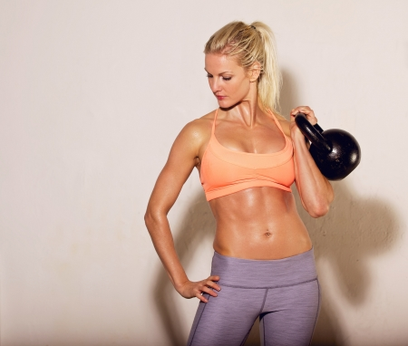 crossfit: Female athlete lifting a kettlebell