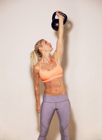 Strong woman lifting a kettlebell with only one hand photo