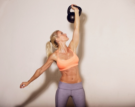 Woman doing her kettlebell crossfit workout photo