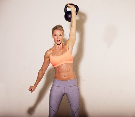 core: Strong crossfit woman doing her kettlebell exercise