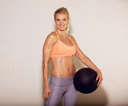 Beautiful pilates instructor holding a fitness ball photo