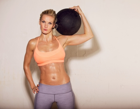 sweaty: Confident female gym instructor carrying a ball on her shoulder