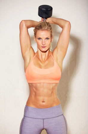 abs: Sweating female athlete working out in the gym