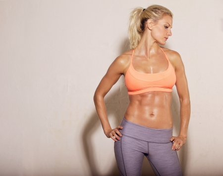 Confident athletic woman with sixpack abs posing photo