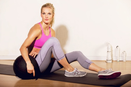 Fitness instructor at the gym sitting on the floor with a pilates ball photo