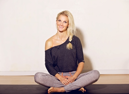 Cheerful blonde woman at the gym sitting on the floor photo