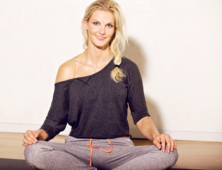 Woman sitting on yoga mat looking happy photo