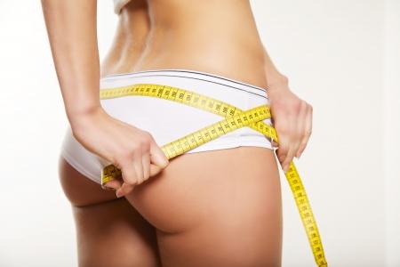 asno: La muchacha en ropa interior blanca que mide su culo y las caderas aislados en un fondo blanco