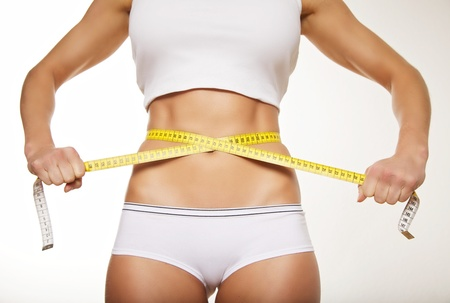 measure waist: Fit beautiful woman holding measure tape around her stomach. Weight loss concept. Stock Photo