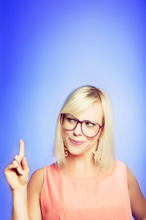 deciding: Smart woman with a good idea, pointing her finger up Stock Photo