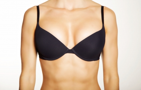 boobs: Closeup of a woman wearing a black bra isolated on white background