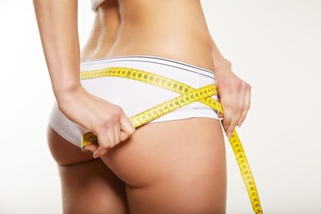 cintura: La muchacha en ropa interior blanca que mide su culo y las caderas aislados en un fondo blanco