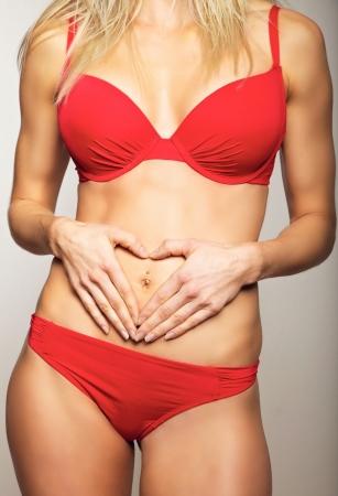 flat stomach: Donna che tiene le mani sul suo ventre piatto facendo un simbolo del cuore Archivio Fotografico