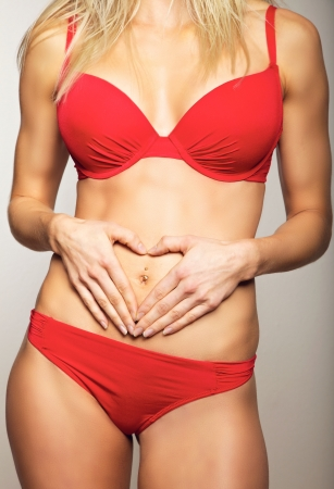 Red panties: Woman holding hands on her flat stomach making a heart symbol
