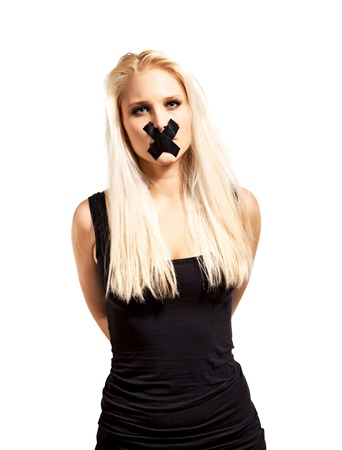 gagged: Portrait of a captive woman tied up and silenced by a tape over her mouth Stock Photo