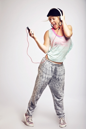 Happy teenager dancing to the beat of hip hop music photo