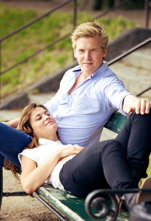 sitting on a bench: Portrait of a sweet guy together with his girlfriend resting on his lap on a park bench