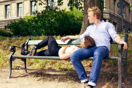 on lap: Romantic young couple resting on the park bench together