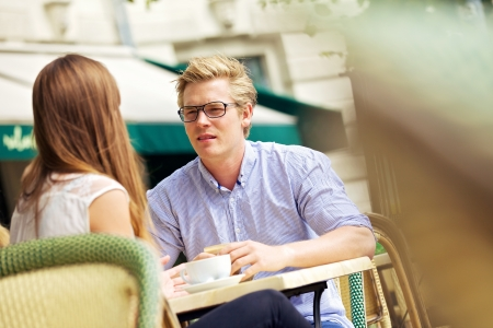 couple talking: Handsome blonde sitting in outdoor cafe listening to his girlfriend