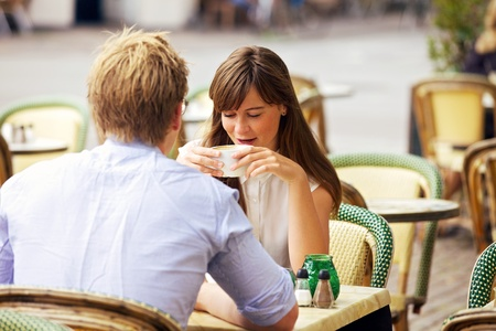 sidewalk talk: Dating couple talking and relaxing together in a Parisian street cafe