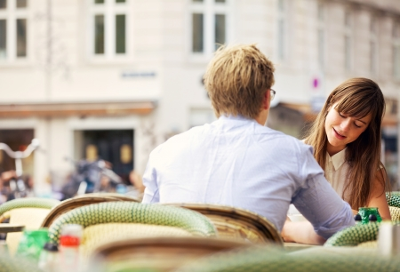 date: Casual woman having a conversation with her date in an open air restaurant
