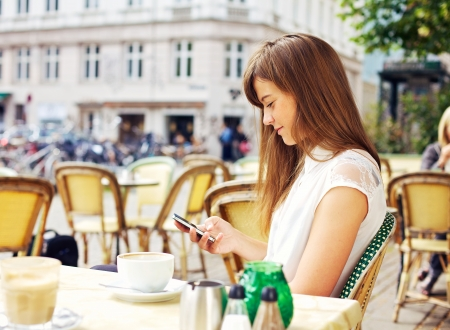 Attractive woman in a street cafe reading a text message from her phone photo