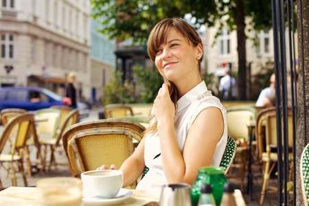 Woman enjoying the pleasant morning with a cup of coffee outdoors in a street cafe photo