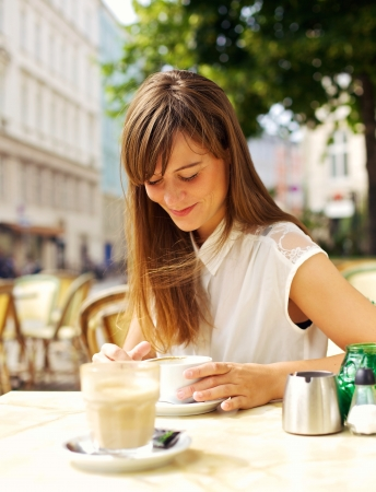coffee shop: Smiling woman enjoying her espresso in an outdoor coffee shop