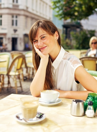 Beautiful relaxed woman smiling and enjoying the open air restaurant in the city photo